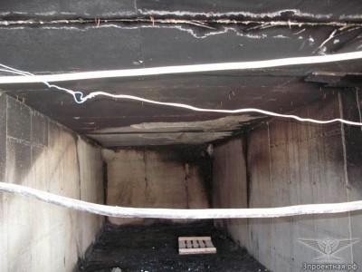 Фото 2. Общий вид на помещение паркинга, в котором располагался очаг пожара (видны участки отслоения защитного слоя бетона, оголения арматуры и копоть на потолке)